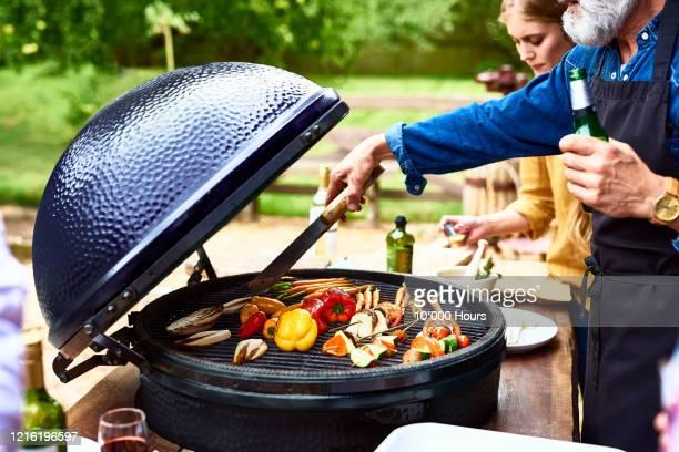 mature man cooking vegetables on barbecue - バーベキューグリル ストックフォトと画像