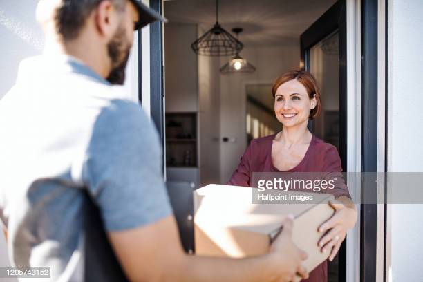 mature man courier delivering parcel to a young woman. - receiving stock pictures, royalty-free photos & images