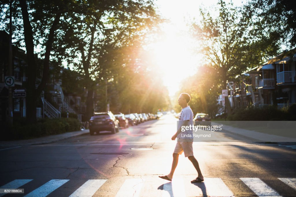 A mature man crossing a street at sunset : Stock Photo