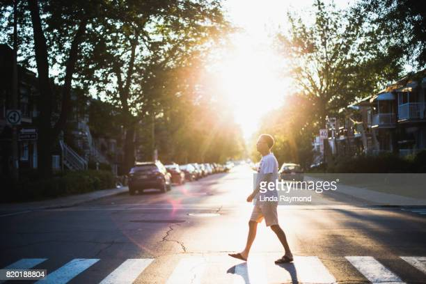 A mature man crossing a street at sunset