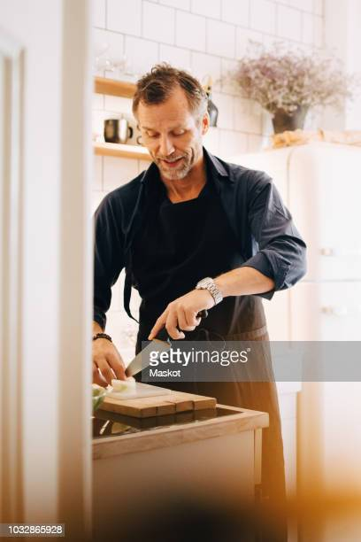 mature man cutting cheese on board at kitchen counter - alleen één oudere man stockfoto's en -beelden