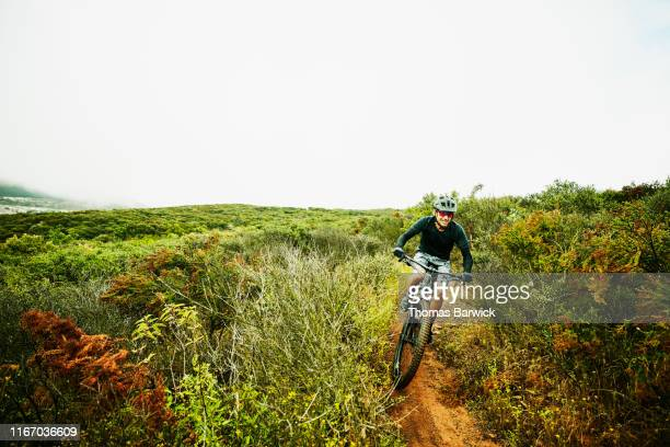 mature man descending down trail during early morning mountain bike ride - forward athlete stock pictures, royalty-free photos & images