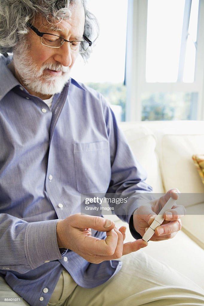 Mature man diabetic testing himself at home : Stock Photo