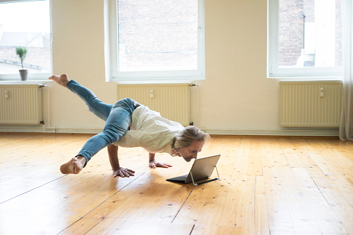 Mature man doing a handstand on floor in empty room looking at tablet - gettyimageskorea