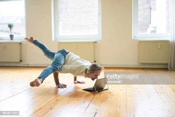 mature man doing a handstand on floor in empty room looking at tablet - net sports equipment stock pictures, royalty-free photos & images