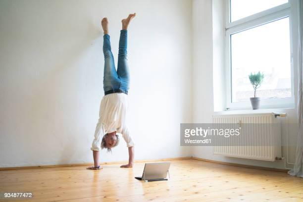 mature man doing a handstand on floor in empty room looking at tablet - handstand stock pictures, royalty-free photos & images