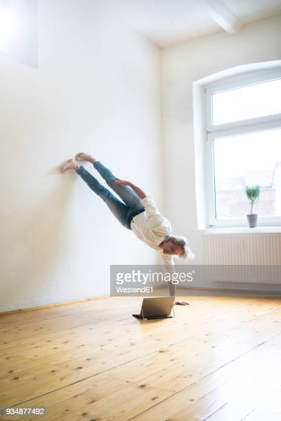 Mature man doing a handstand on floor in empty room looking at tablet