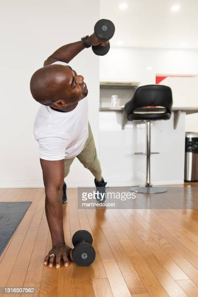 "mature man doing exercise at home. - ""martine doucet"" or martinedoucet stock pictures, royalty-free photos & images"