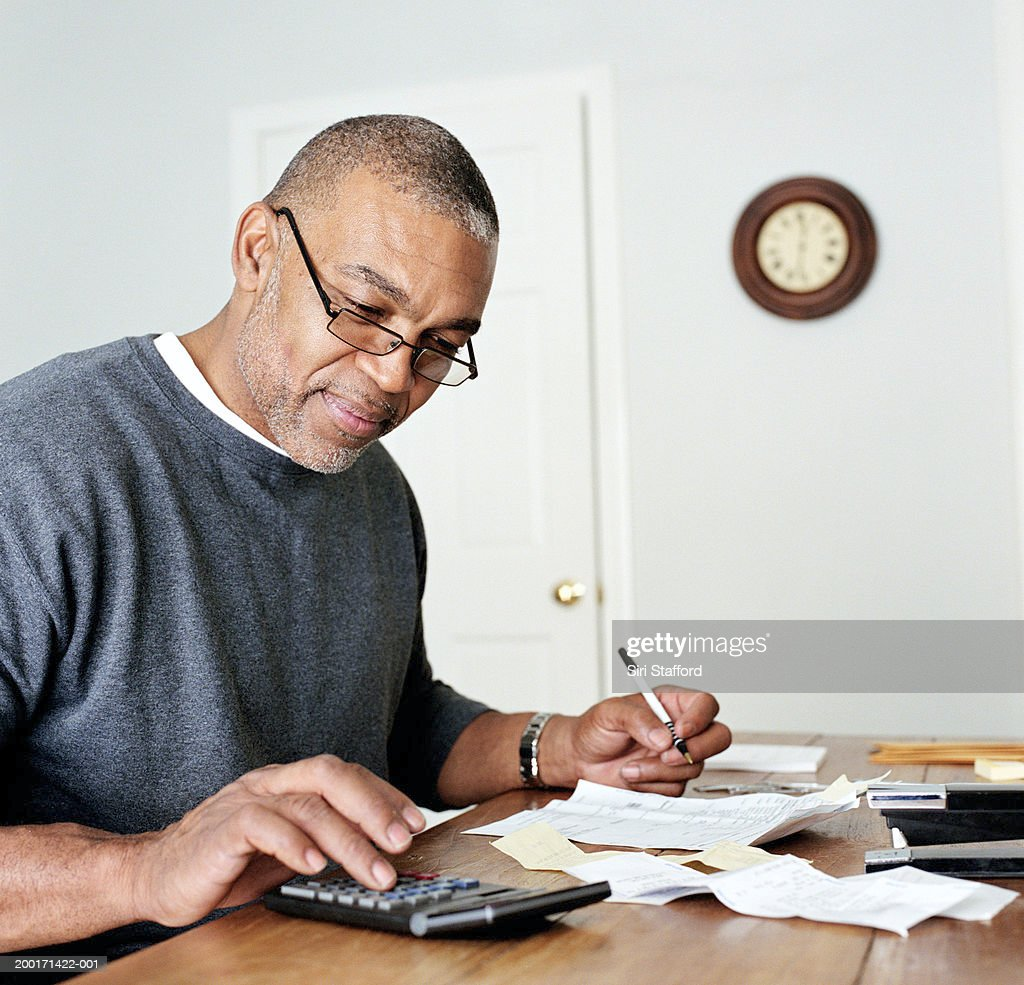 Mature man doing finances in home office : Stock Photo