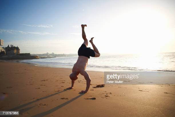 Mature man doing handstand on sunlit beach, Cascais, Portugal