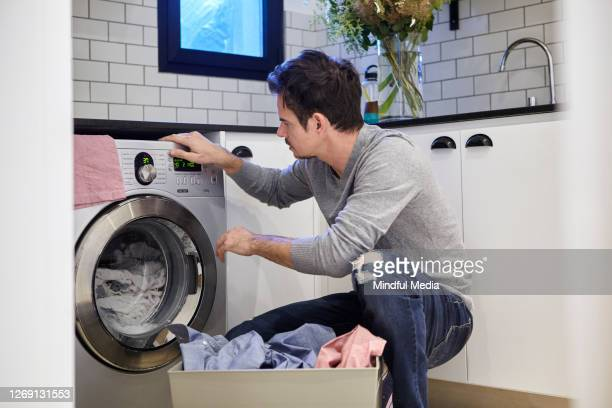mature man doing laundry - washing machine stock pictures, royalty-free photos & images