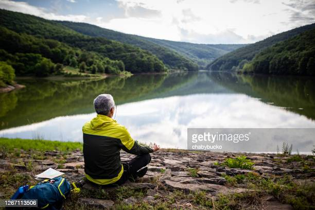 mature man doing meditation by the lake - one mature man only stock pictures, royalty-free photos & images