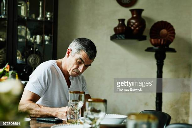 Mature man doing paperwork at table in dining room