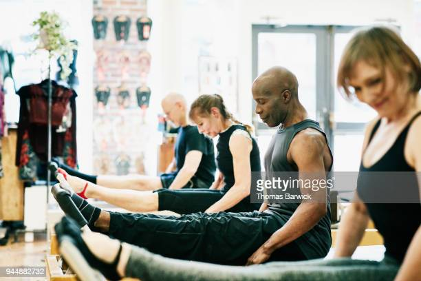 Mature man doing pilates reformer exercises during class in pilates studio