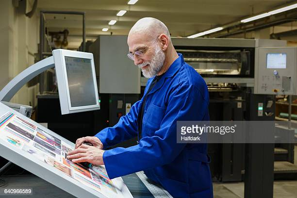 Mature man doing quality check of printout with scanner at printing press