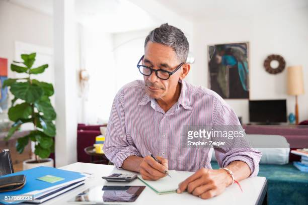 mature man doing working at home - economia fotografías e imágenes de stock