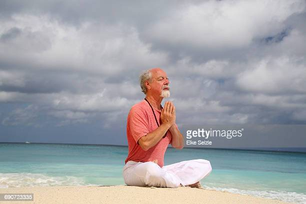 mature man doing yoga at pristine beach - yogi stock photos and pictures