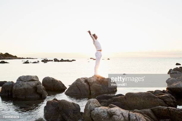 Mature man doing yoga exercise on a rock at the sea