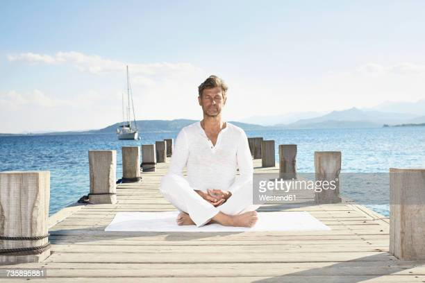 Mature man doing yoga exercise on jetty