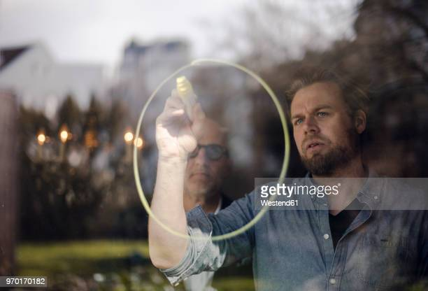 mature man drawing a circle on window pane, senior man watching - circle stock pictures, royalty-free photos & images