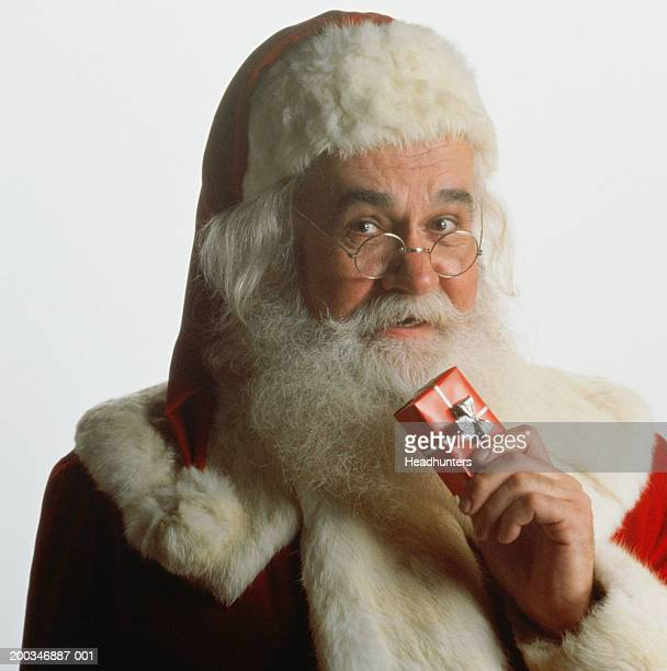 mature man dressed as santa claus holding gift - fur trim stock pictures, royalty-free photos & images