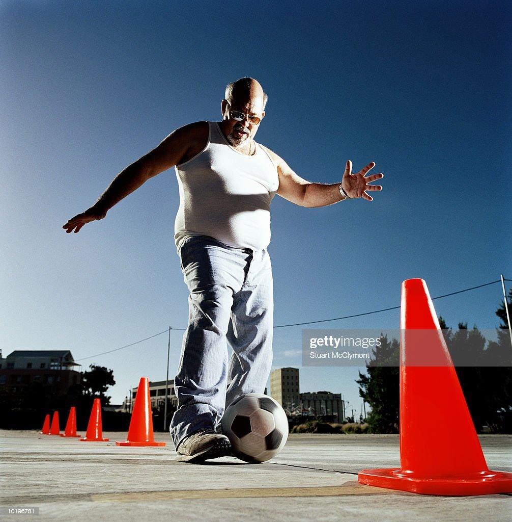 Mature man dribbling ball through cones : ストックフォト
