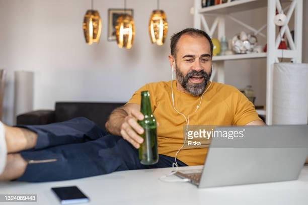 mature man drinking beer and watching a sport match on the laptop - international team soccer stock pictures, royalty-free photos & images