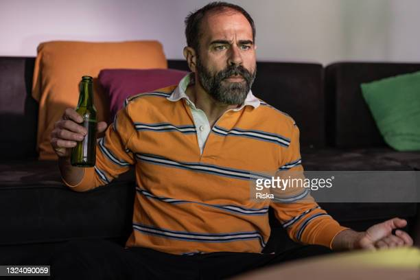 mature man drinking beer and watching a sport match on the tv - international team soccer stock pictures, royalty-free photos & images
