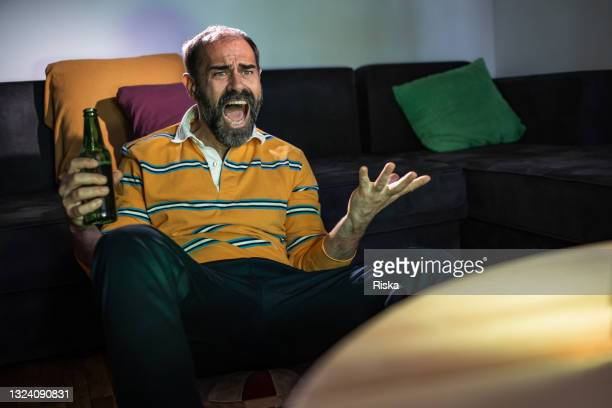 mature man drinking beer and watching a sport match on the tv - world sports championship stock pictures, royalty-free photos & images