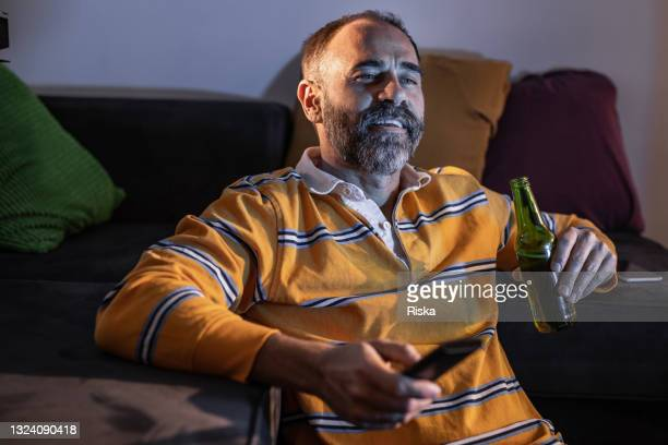 mature man drinking beer and watching tv - international team soccer stock pictures, royalty-free photos & images