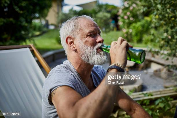 mature man drinking beer from bottle in garden - trinken stock-fotos und bilder
