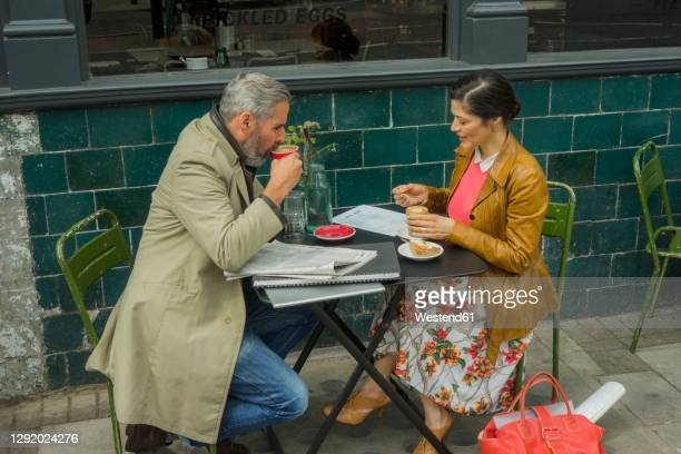 mature man drinking coffee while sitting with woman at cafe - newspaper stock pictures, royalty-free photos & images