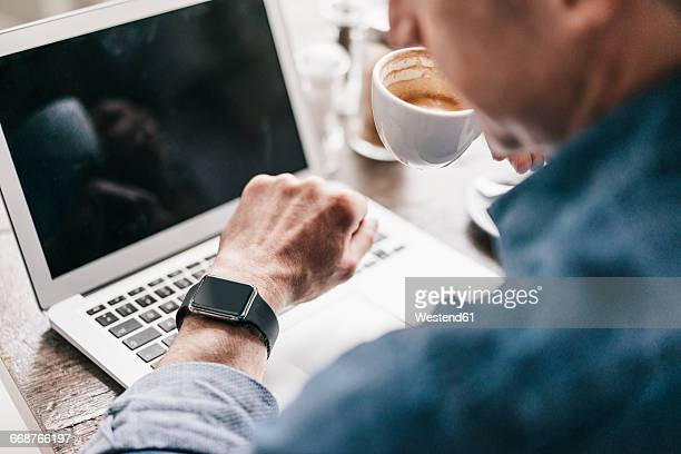Mature man drinking coffee while working at laptop, looking at smartwatch