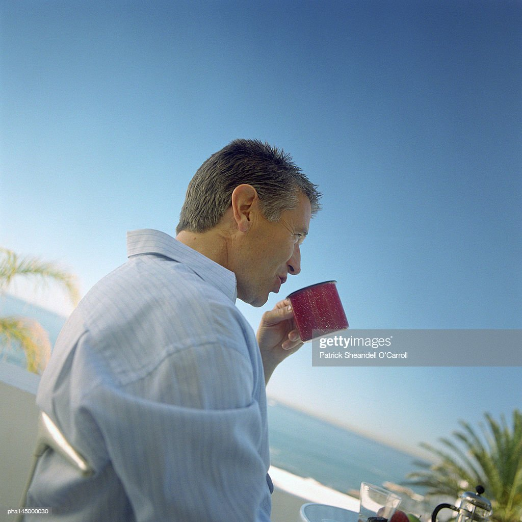 Mature man drinking from mug, side view : Stockfoto