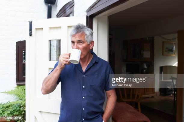 mature man drinking tea in the doorway of his house - só um homem idoso - fotografias e filmes do acervo