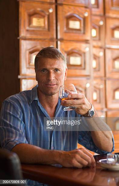 Mature man drinking whiskey at cigar bar, smiling, portrait