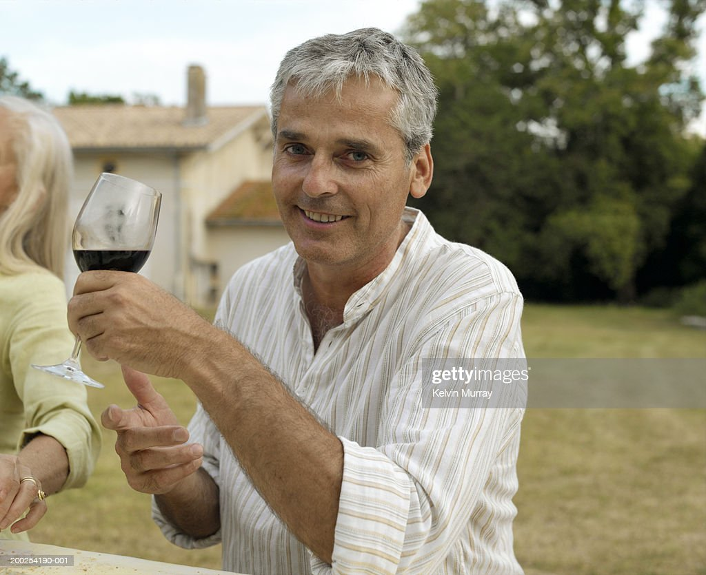 mature man drinking wine at outdoor table smiling portrait stock