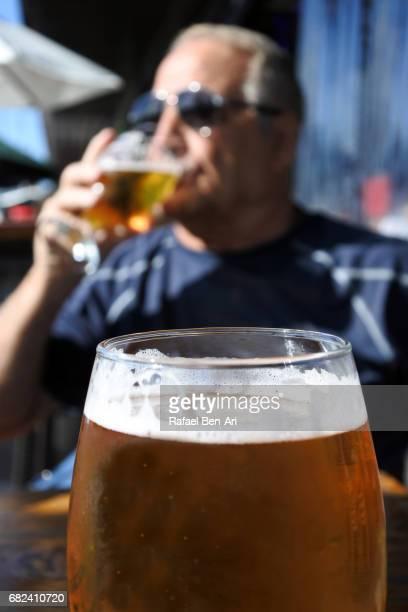 Mature man drinks fresh beer