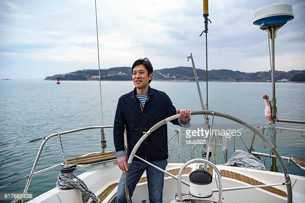 Mature man driving a lusury yacht