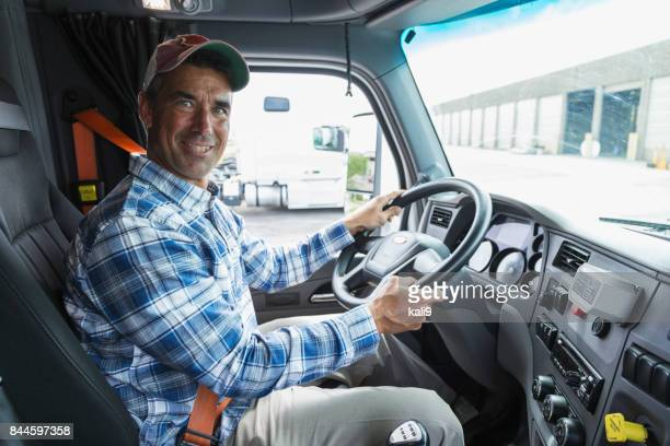 Mature man driving a truck outside warehouse