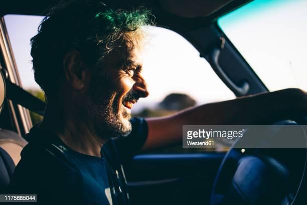 mature man driving at sunset - driving ストックフォトと画像
