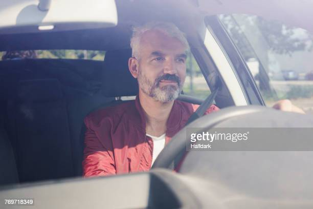 Mature man driving car seen through windshield