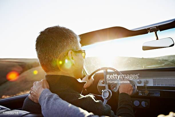 mature man driving convertible at sunset - convertible stock pictures, royalty-free photos & images
