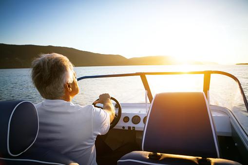 mature man driving speedboat 499335482