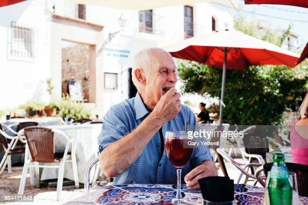 Mature man eating and drinking outside in cafe