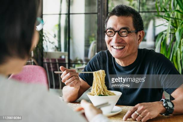 mature man eating bowl of noodles and laughing - noodles stock pictures, royalty-free photos & images