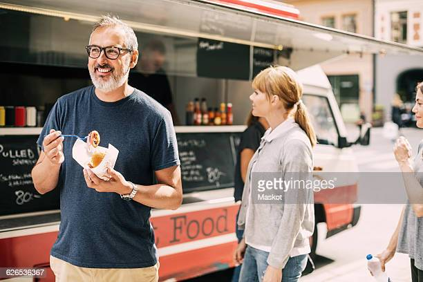 mature man eating food while standing against truck at street - food truck fotografías e imágenes de stock