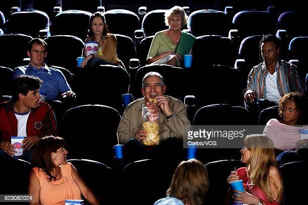 Mature Man Eating Potato Chips in Movie Theater Auditorium