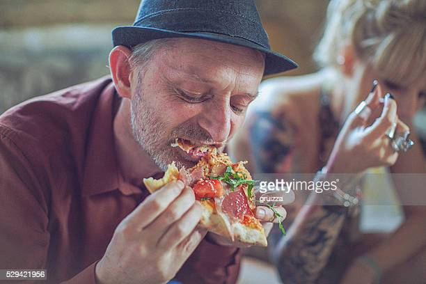 Mature man eating slice of pizza