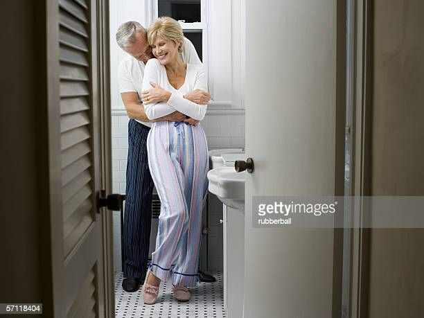 Mature man embracing a mature woman in the bathroom